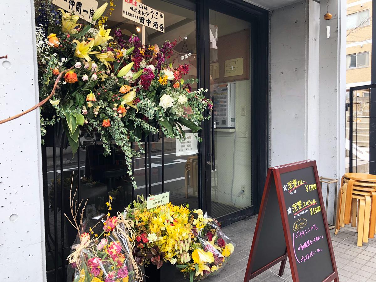 カレーショップ【涅槃】は2月8日にオープンしたばかり、え、パンニャの松尾さんから花が来てるー