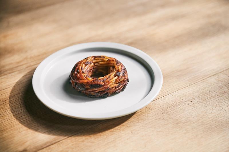 <ドーナツパスタ ボロネーゼ> パスタの定番ミートソースを丸ごと閉じ込めた、シグネチャーメニュー。 慣れ親しんだ味わいと驚きのある新しい食感をお楽しみください。