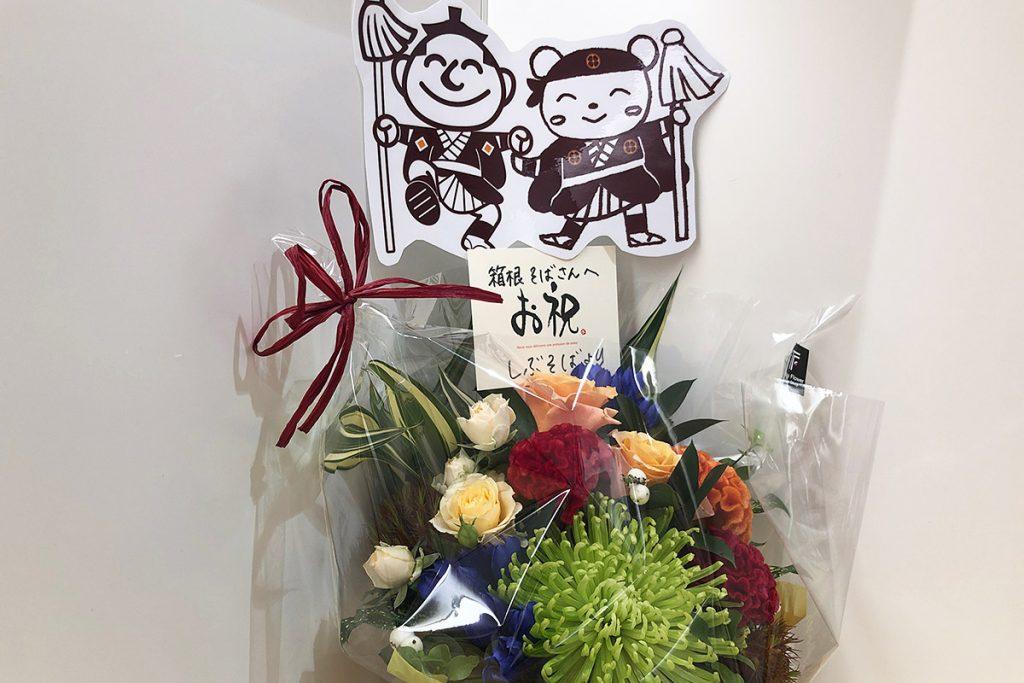 お店に送られていたお花、よく見たらしぶそばさんからでした。しぶそばは東急系列の駅そばのお店ですよね。系列を超えて祝ってもらえるのはうれしいですねー。両方のお店のキャラが並んでいるイラストにほっこりします