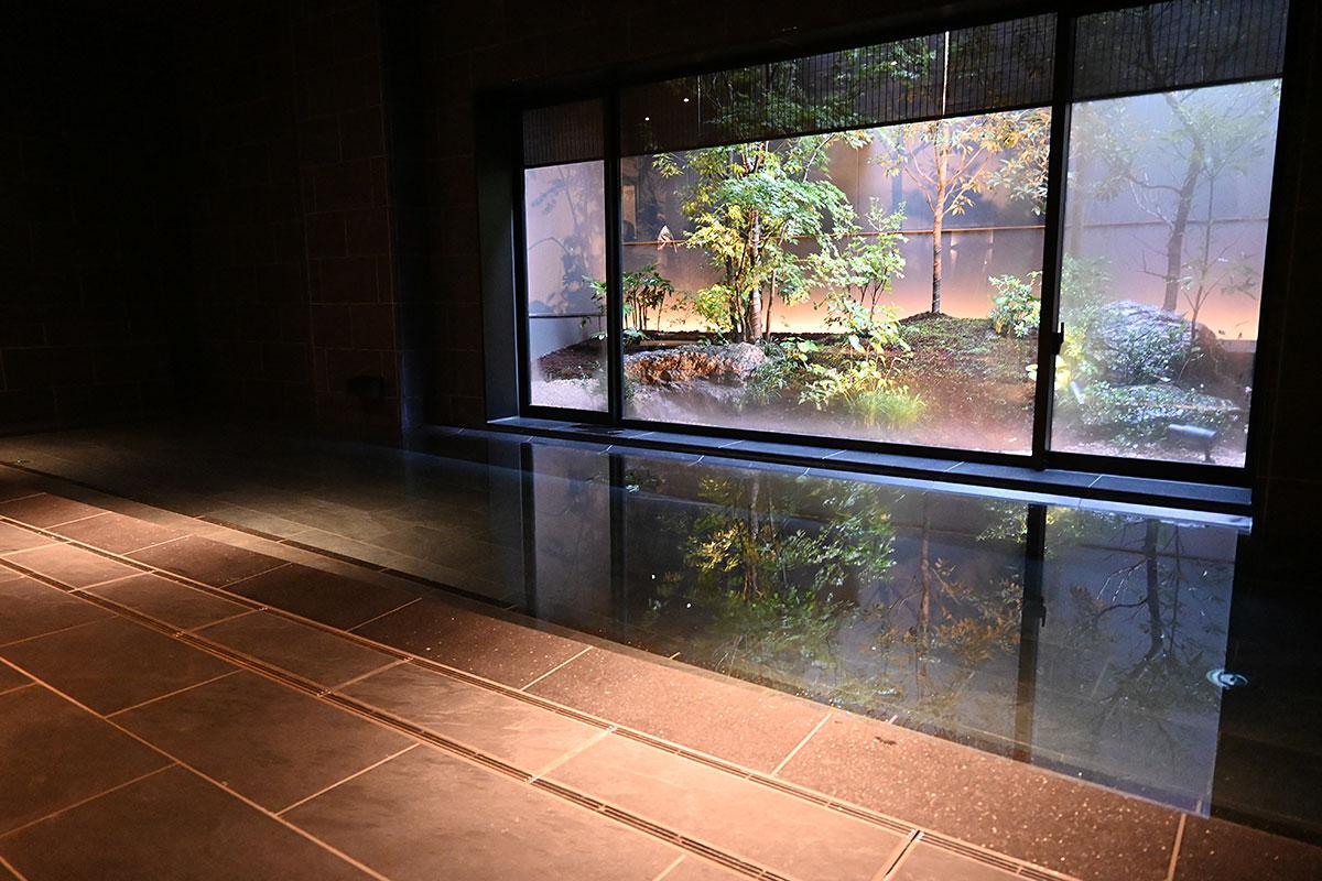 落ち着きのある照明、庭園が一望できるメインの浴槽